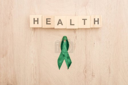 top view of cubes with health lettering and green ribbon on wooden background