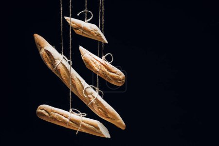 Photo for Loaves of fresh baked baguettes on ropes isolated on black - Royalty Free Image