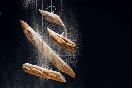 Photo for White flour and loaves of fresh baked baguettes on ropes on black background - Royalty Free Image