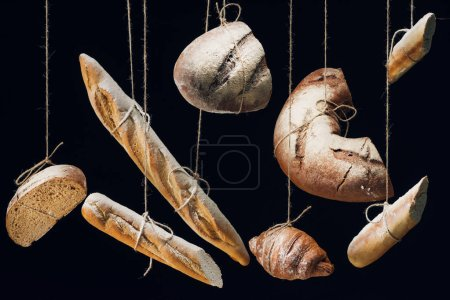 fresh baked bread, baguettes and croissant with flour hanging on ropes isolated on black