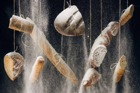 Photo for Flour falling at bread, baguettes and croissant hanging on ropes on black background - Royalty Free Image