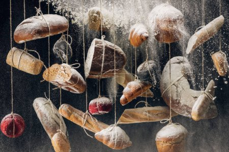 Photo for Flour falling at loaves of white and brown bread and pastry hanging on ropes - Royalty Free Image