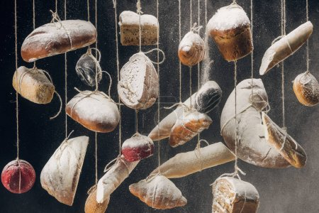 Photo for Flour falling at fresh homemade bread and pastry hanging on ropes - Royalty Free Image