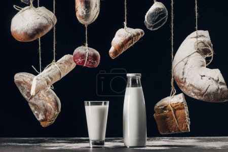 Photo for Milk on table and bread with flour hanging on strings isolated on black - Royalty Free Image