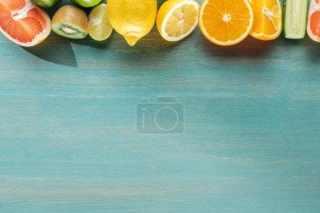 Photo pour Vue de dessus des fruits juteux sur la surface texturée bleue - image libre de droit