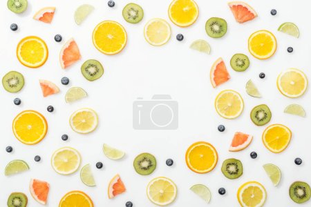 Photo for Top view of cut fruits and blueberries on white surface - Royalty Free Image