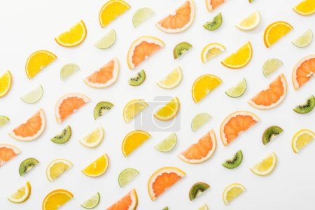 Photo for Flat lay with juicy cut fruits on white surface - Royalty Free Image