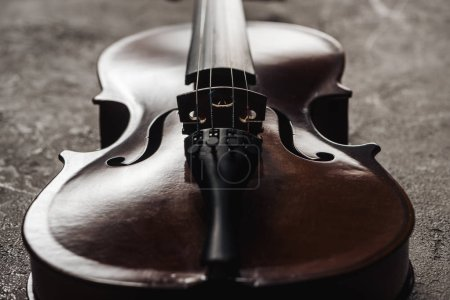 Photo for Close up of classical wooden cello on grey textured background in darkness - Royalty Free Image