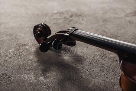 Photo pour Fermez-vous vers le haut des cordes sur le violoncelle classique sur le fond texturé gris - image libre de droit