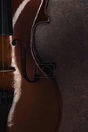 Foto de Vista superior de violonchelo clásico sobre superficie gris texturizada en la oscuridad - Imagen libre de derechos