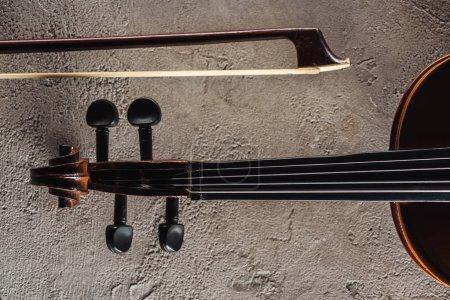 Photo pour Vue de dessus de violoncelle classique et arc sur la surface texturée grise - image libre de droit