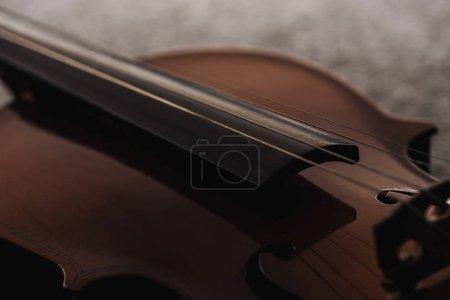 Photo pour Gros plan de cordes sur violoncelle en bois dans l'obscurité sur fond gris texturé - image libre de droit