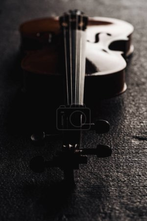 Photo pour Gros plan de cordes sur violoncelle dans l'obscurité sur fond gris texturé - image libre de droit