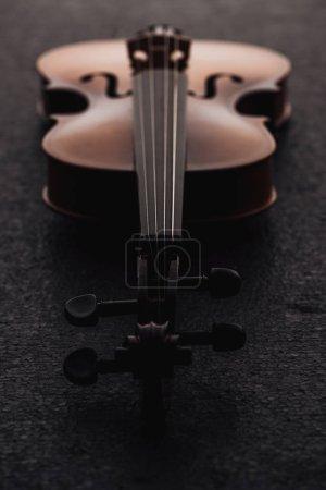 Photo pour Gros plan de cordes sur violoncelle dans l'obscurité sur surface grise texturée - image libre de droit