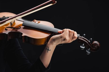Foto de Cropped view of woman with tattoo playing cello with bow isolated on black - Imagen libre de derechos