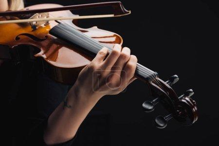 Photo pour Vue recadrée de femme tatouée jouant le violoncelle avec l'arc isolé sur le noir - image libre de droit