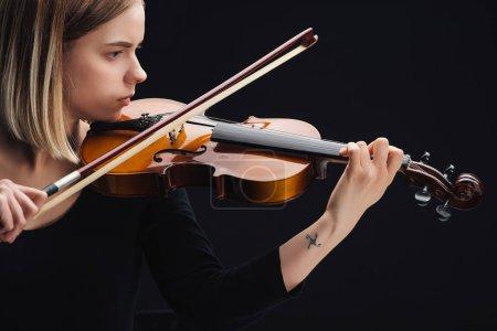 Photo pour Jeune femme tatouée jouant du violoncelle avec arc isolé sur noir - image libre de droit