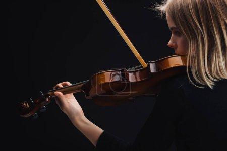 Photo pour Jeune femme concentrée jouant du violoncelle avec arc isolé sur noir avec espace de copie - image libre de droit