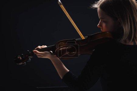 Photo pour Jeune femme concentrée jouant le violoncelle avec l'arc dans l'obscurité isolée sur le noir - image libre de droit