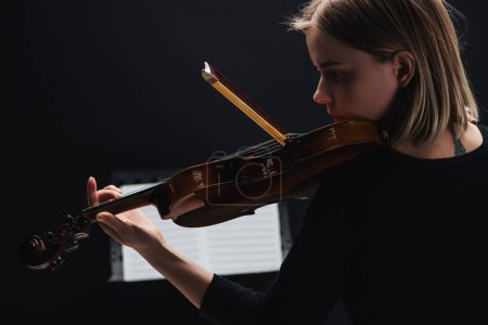 Foto de Selective focus of young concentrated woman playing cello with bow in darkness with music book at background isolated on black - Imagen libre de derechos