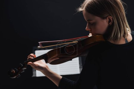 Foto de Selective focus of young woman playing cello with bow in darkness with music book at background isolated on black - Imagen libre de derechos