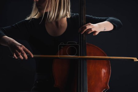Photo for Cropped view of young woman playing double bass in darkness isolated on black - Royalty Free Image