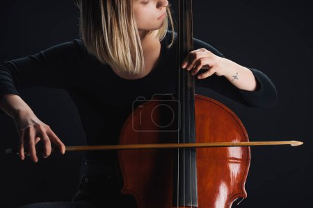 Photo pour Vue partielle de femme tatouée jouant de la contrebasse dans l'obscurité isolé sur noir - image libre de droit