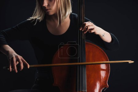 Photo for Cropped view of tattooed woman playing double bass in darkness isolated on black - Royalty Free Image