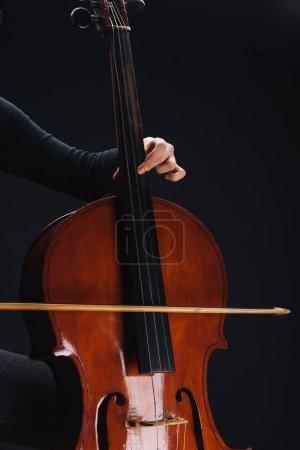 Photo pour Vue recadrée de femme jouant de la contrebasse dans l'obscurité isolé sur noir - image libre de droit