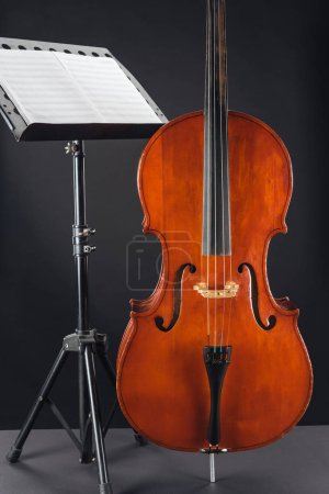 Photo for Classic wooden double bass near opened music book on stand on black background - Royalty Free Image