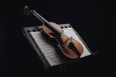 Photo for Classic wooden cello on opened music book on stand isolated on black - Royalty Free Image