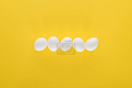 Photo pour Cinq œufs de poulet blanc en rangée sur fond jaune - image libre de droit