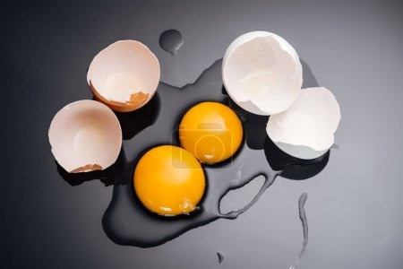 Photo for Top view of raw smashed chicken eggs with yolks, proteins and eggshell on black background - Royalty Free Image