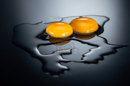 Photo for Raw chicken yolks and proteins on black background - Royalty Free Image