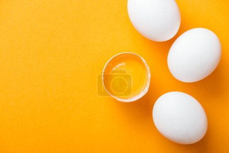 Photo for Top view of smashed chicken egg with yolk on bright orange background among white whole eggs - Royalty Free Image