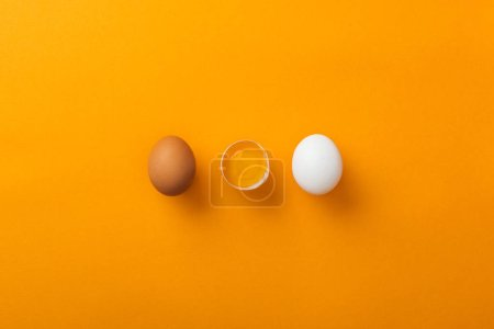 Photo for Top view of two whole chicken eggs with smashed one on bright orange background - Royalty Free Image