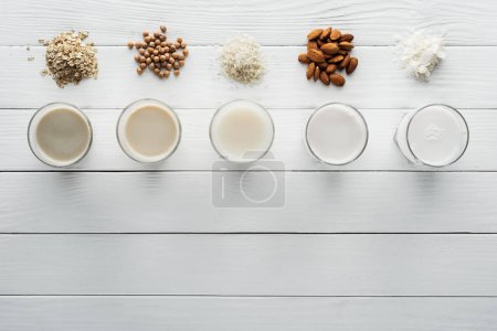 Photo for Top view of glasses with coconut, chickpea, oat, rice and almond milk on white wooden surface with ingredients - Royalty Free Image
