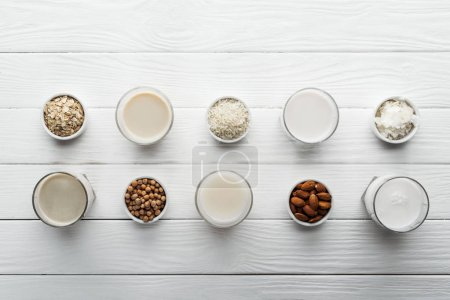 top view of glasses with coconut, chickpea, oat, rice and almond milk on white wooden table with ingredients in bowls