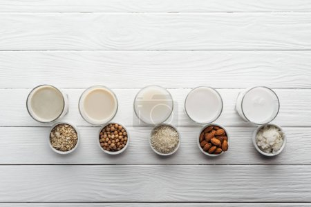 Photo for Top view of glasses with coconut, chickpea, oat, rice and almond milk with ingredients in bowls - Royalty Free Image