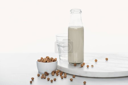 Photo for Chickpea milk in bottle near chickpea in bowl and empty glass isolated on white - Royalty Free Image