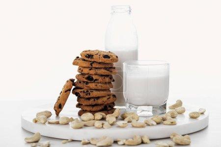 Photo pour Lait de cajou végétalien en verre et bouteille près de biscuits au chocolat d'isolement sur le blanc - image libre de droit