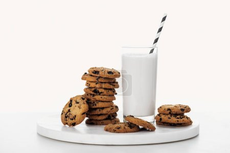 Photo for Pile of tasty chocolate cookies near glass with milk and straw isolated on white - Royalty Free Image