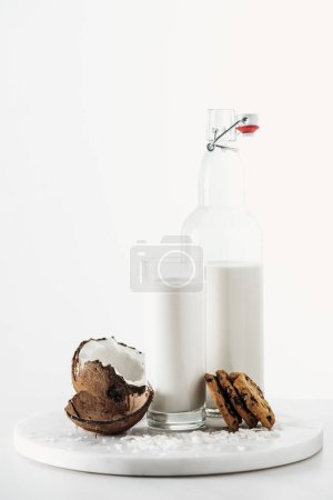 Photo for Coconut vegan milk in glass and bottle near coconut and chocolate cookies isolated on white - Royalty Free Image