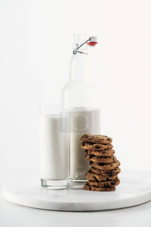 Photo for Pile of tasty chocolate cookies near bottle and glass with fresh milk isolated on white - Royalty Free Image