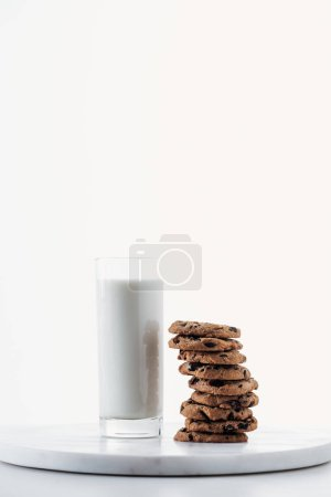 Photo for Fresh milk in glass near chocolate cookies on marble stand isolated on white - Royalty Free Image