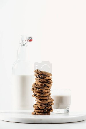 Photo for Fresh milk in glass and bottle near chocolate cookies on marble stand isolated on white - Royalty Free Image