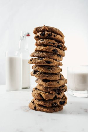 Photo for Selective focus of chocolate cookies near bottle and glasses with milk on marble table - Royalty Free Image