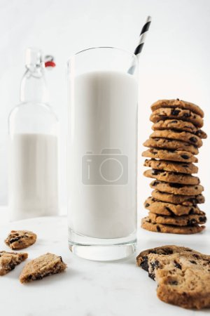 Photo for Selective focus of glass with fresh milk and straw near chocolate cookies and bottle on marble table - Royalty Free Image