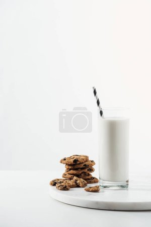 Photo for Glass with fresh milk and straw near chocolate cookies on marble stand isolated on white - Royalty Free Image