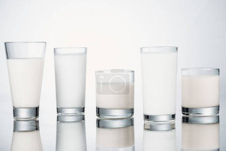 row of glasses with organic fresh vegan milk on grey background with reflection